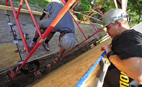 Sailors from USS Independence use a chalk line to mark a stud behind the wall of a Habitat for Humanity project house.
