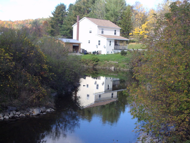 River reflections in Vermont of a cottage