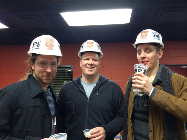 Three men in hard hats, holding beers. One in safety goggles. One has since passed away, and the rest of us are pretty devastated.