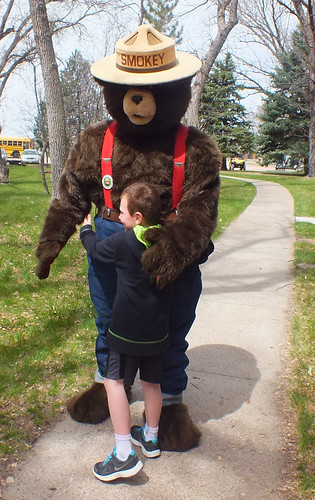 Smokey Bear gets a hug from a child from Sandhills Public School in Nebraska. More than 100 people turned out to tour the Bessey Nursery. (U.S. Forest Service/Tim Buskirk)