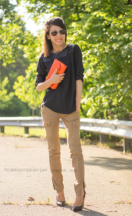 black faux leather yoke top, cargo pants, orange clutch, wooden heeled pumps