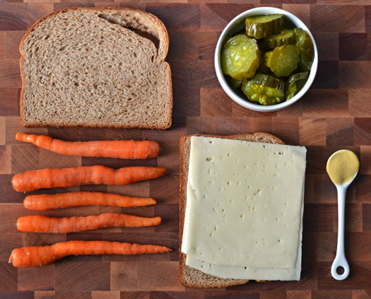 Ingredients to make a roasted carrot grilled cheese on a cutting board