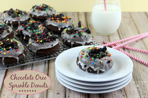 Chocolate Oreo Sprinkle Donuts on cooling rack with one donut on a stack of plates with a glass of milk.