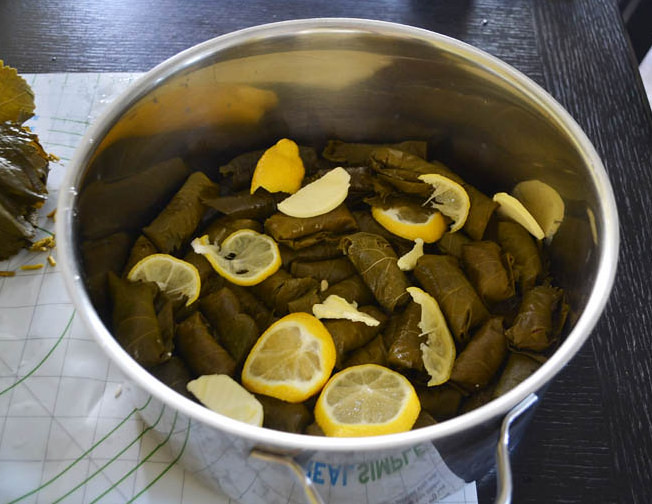 Lay grape leaf rolls along the bottom of a pot layered with lemon slices.