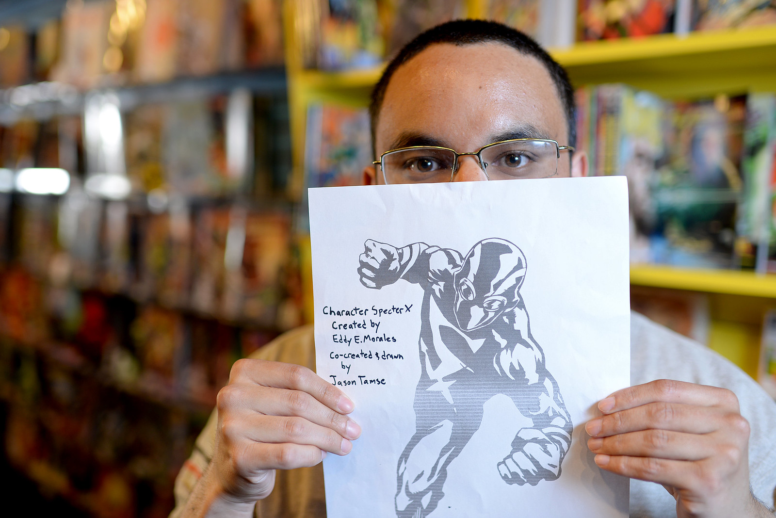 """Eddy Enrique Morales, alumnus of SF State with a BA in drama, holds up a drawing of Specter X, a character he created and calls """"San Francisco's first and very own Latino superhero."""" Morales aims to have his first comic, featuring Specter X, come out early 2014 with the help of funds he received through a fundraising website and the San Francisco community. Photo by Virginia Tieman / Xpress"""