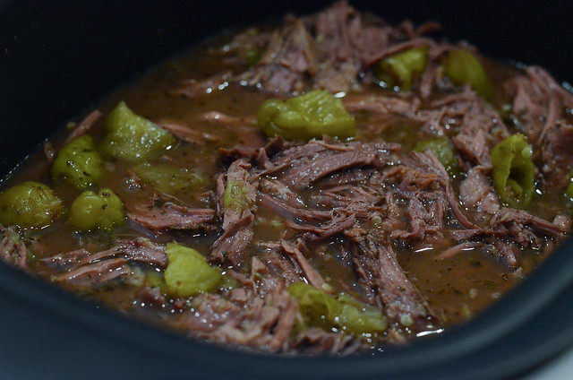 Cooked shredded beef and pepperoncini in a slow cooker.