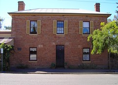 Heritage listed Georgian style box shaped house in main street of Nairne. 12 paned windows, shutters, perfect proportions and symmetry. Built for Henry Timmins a tanner. 3 paned fan light above doorway. Probably built in 1851 when Timmins opened his tanne