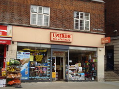 "A terraced shopfront with a sign reading ""UNIKOB the stationer"".  Various items of stationery and craft supplies are visible in the shop windows."