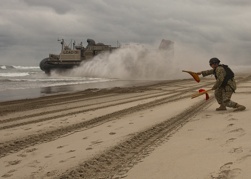 Boatswain's Mate 3rd Class Bryan Dingess, assigned to BMU 1, signals to a landing craft, air cushion (LCAC)