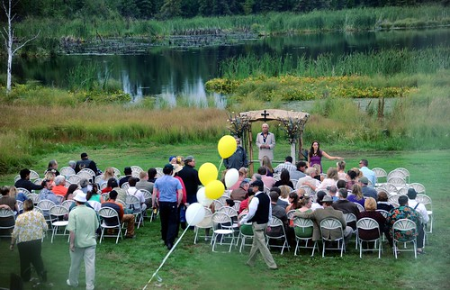 Wedding in the open, seated friends and family, bower, cross, white and yellow ballons, wedding of Jessie and Chris, Fairbanks, Alaska, USA by Wonderlane