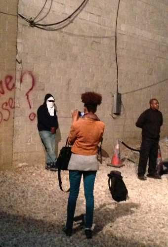 People taking pictures near Banksy paintings, 24th St.