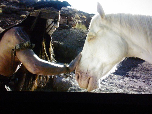 Tonto (Johnny Depp) wearing crow crown, petting Silver (played by Silver an 11 yr old quarter horse - upstaging everyone), a white spirit horse, The Lone Ranger, film, Northgate, Seattle, Washington, USA by Wonderlane
