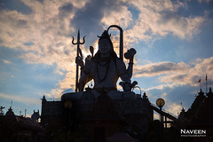 Giant Shiva statue with surreal sunset background