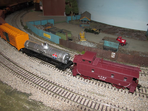A 1950's and 60's era Santa Fe freight train rounds the mainline curve alongside the scrap yard. by Eddie from Chicago