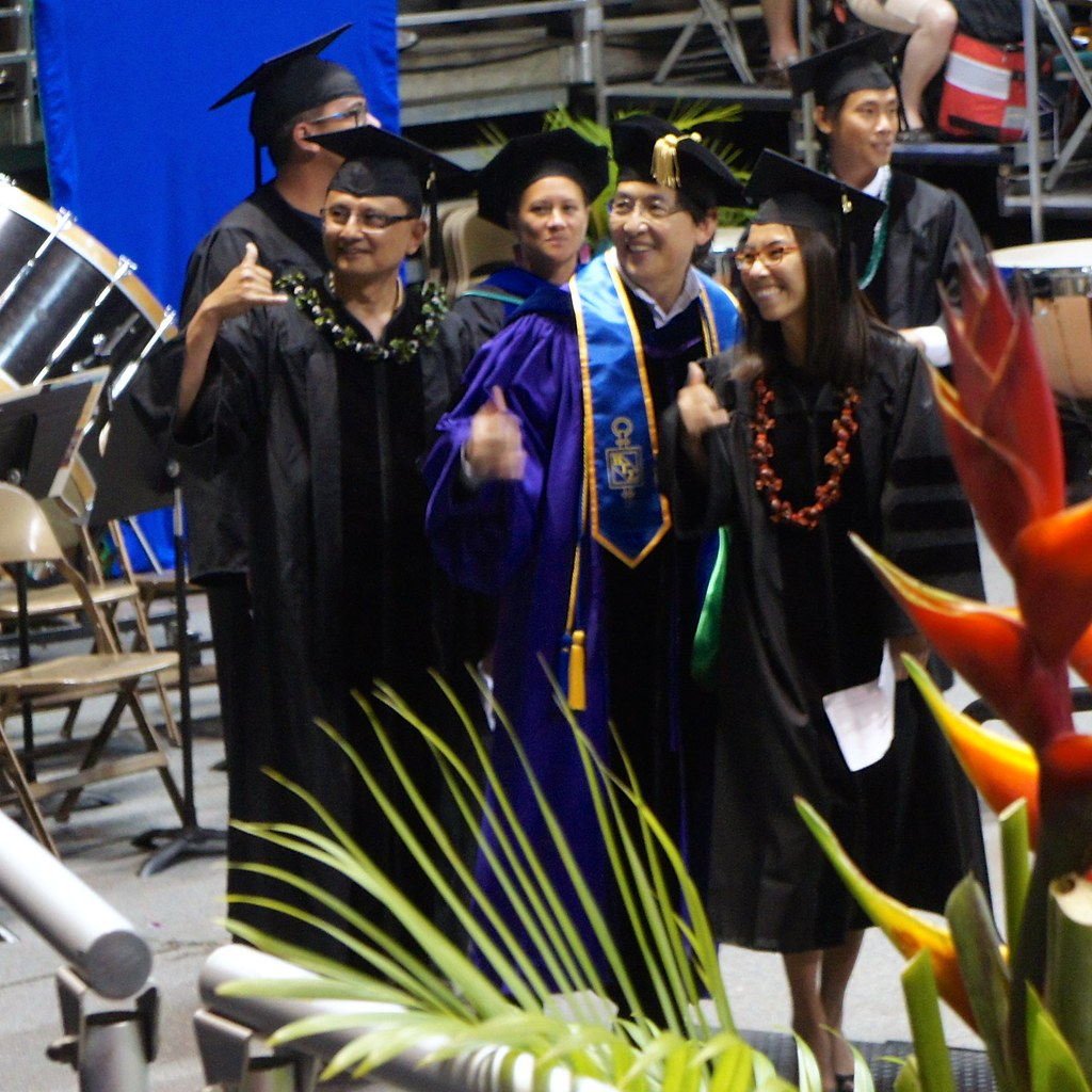 <p>Three shakas from University of Hawaii at Manoa Shidler College of Business Information Technology Management Professor Tung Bui and two of his communication and information sciences PhD graduates at the University of Hawaii and Manoa commencement ceremony at the Stan Sheriff Center on May 17, 2014. Photo by Andrew Wertheimer.</p>