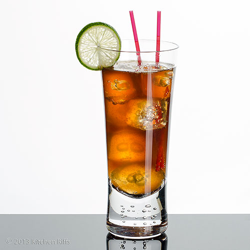 Cuba Libre Cocktail in tall glass with straws and lime garnish