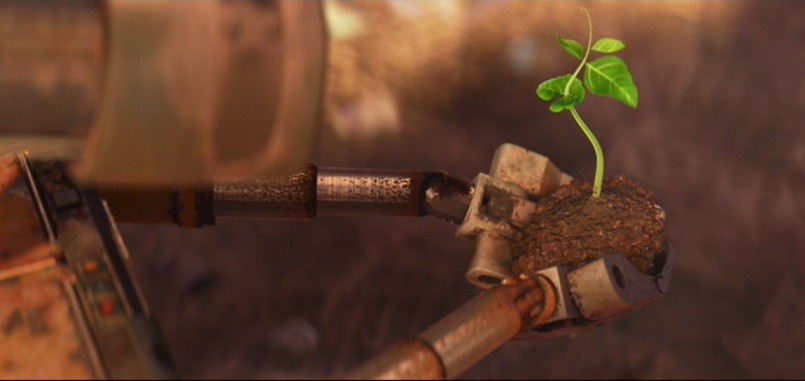Image from film WALL-E, robot holds small piece of soil with a small plant sprouting up from it.