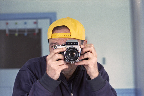 reflected self-portrait with Exakta VX1000 camera and yellow baseball cap by pho-Tony