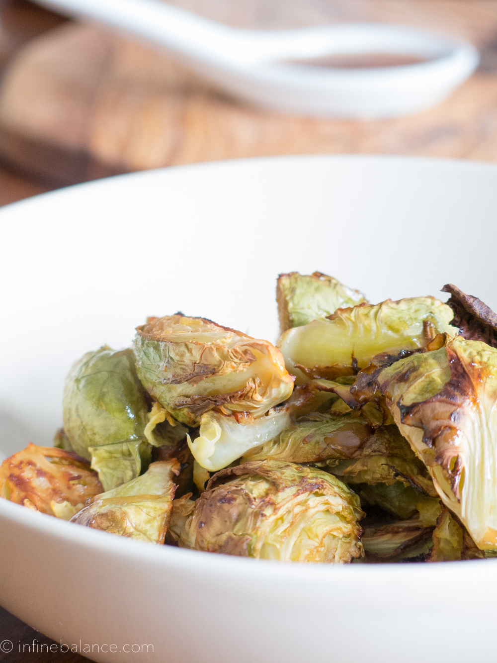 close up of oven roasted brussel sprouts with miso glass in a white bowl
