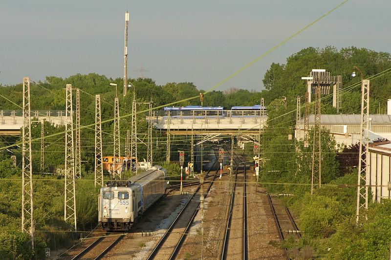 Während der C2-Zug auf seine Überführung nach Wegberg wartet, überquert ein Buszug des U6-Schienenersatzverkehrs den Eisenbahnnordring auf der Fahrt anch Fröttmaning