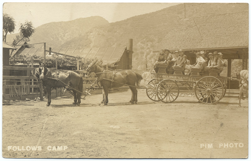 View of horse-drawn wagon loaded with passengers in Follows Camp in the San Gabriel Mountains