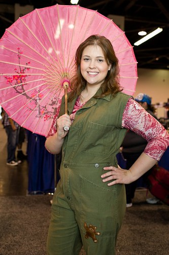 A cosplayer dresses as Kaylee from Firefly with a pink parasol