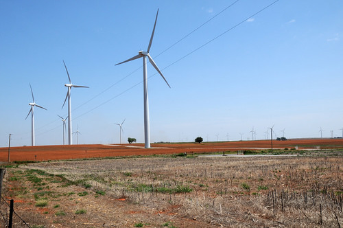 A tractor tills the soil among wind turbines in Oklahoma on August 13, 2009. USDA photo by Alice Welch.