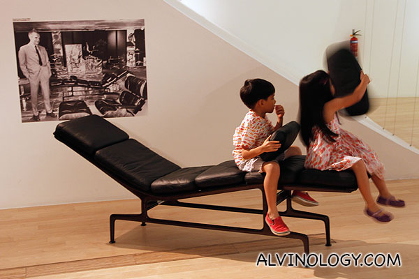 Two kids playing on a Eames designed lounge chair