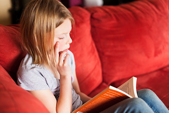 A 7 Year old reading on a red couch