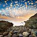 弹好的棉花,飘到天上,成了云;未弹的,掉在地上,成了石头。太阳出来了,把它们染成了斑斓。