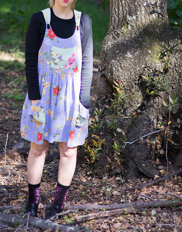 floral lavender pinafore dress with pockets over black long-sleeved shirt, black socks