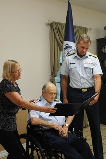 Donald Brackett, Coast Guard Auxiliary, is shown with his daughter Carol Spooner, and Rear Adm. Jake Korn, Seventh Coast Guard District commander, as he is read his Auxiliary Meritorious Service Medal citation at is home in Pinellas Park, Fla., Wednesday, Sept. 25, 2013. Brackett joined the Auxiliary in 1947 and had served for 66 years. U.S. Coast Guard photo by Petty Officer 1st Class Crystalynn A. Kneen