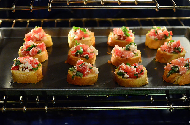 Baking sheet with Feta Bruschetta inside an oven.
