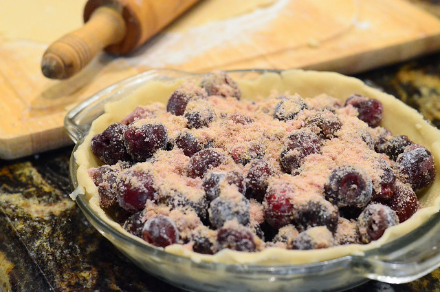 A pie dish with pie crust has the cherry filling added to it.