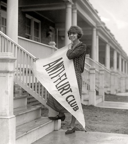 "A girl holding a pennant that reads ""anti-flirt club"" in the 1920s"