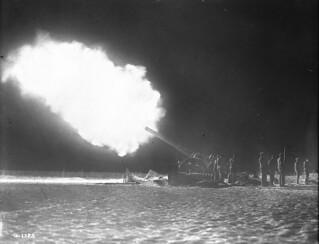 A naval gun behind Canadian lines firing in the night over Vimy Ridge, France, 1917 / Un canon naval placé derrière les lignes canadiennes fait feu sur la crête de Vimy (France) pendant la nuit, en 1917