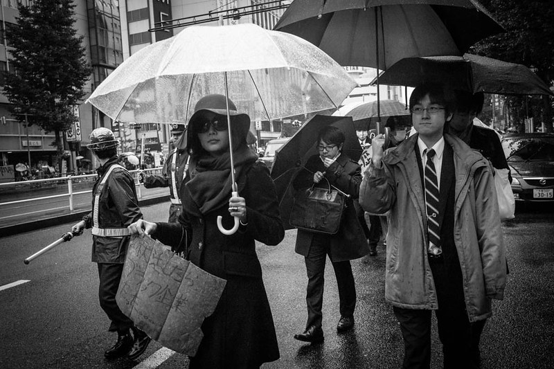 A group of protestors walking in the rain on the streets of Tokyo.
