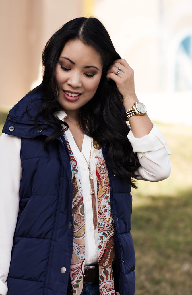 cute & little blog | navy quilted puffer vest, white blouse, tassel necklace, paisley scarf, skinny jeans | fall trend layering outfit