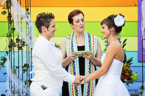 The two brides, dressed in white, in front of a house painted like a rainbow