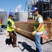 Workers unloading glass tubing necessary for sulfuric acid creation by Mississippi Power's Kemper County energy facililty