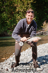 A middle-aged man holds up a rainbow trout after c…