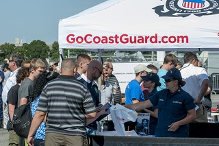 Coast Guard members pass out recruiting information to community members at Coast Guard Sector St. Petersburg, Fla., during the sector's open house Saturday, May 17, 2014. The open house kicked off National Safe Boating Week and raised boating safety awareness for the St. Petersburg community. (U.S. Coast Guard photo by Petty Officer 2nd Class Michael De Nyse)