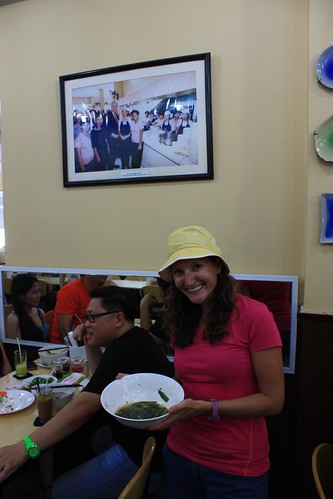 Lina with her Pho in front of a picture of Bill Clinton with his Pho