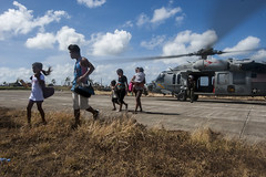 Civilians exit an MH-60S Seahawk from Helicopter Sea Combat Squadron (HSC) 12 in Guiuan after being airlifted during Operation Damayan, Nov. 15. (U.S. Navy photo by Mass Communication Specialist Seaman Liam Kennedy)