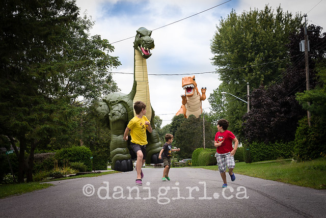 Photo of children pretending to run from a toy dinosaur