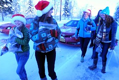 Pretty playful Santas, smiling community volunteers out to spred Christmas joy to the world - distributing hot cider, cookies, candy, and other goodies, on a cold day with snow, Rosie is behind them all the way, Anchorage, Alaska, USA