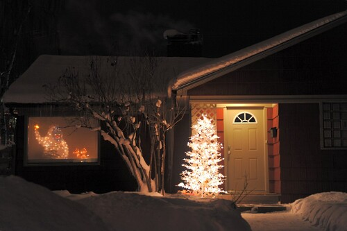 White lighted Christmas tree outside, white lighted blue faced yeti inside, two lighted deer, chimney smoke, house, night, snow, South Addition, Anchorage, Alaska, USA by Wonderlane