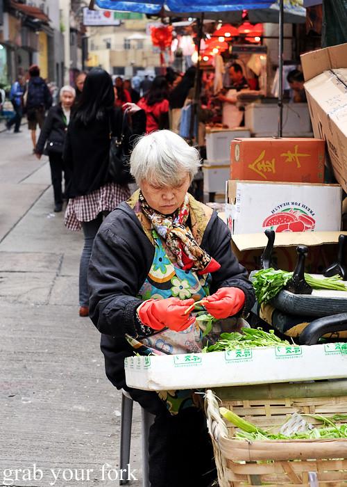 Market staller holder trimming vegetables at the Graham Street market, Central district, Hong Kong