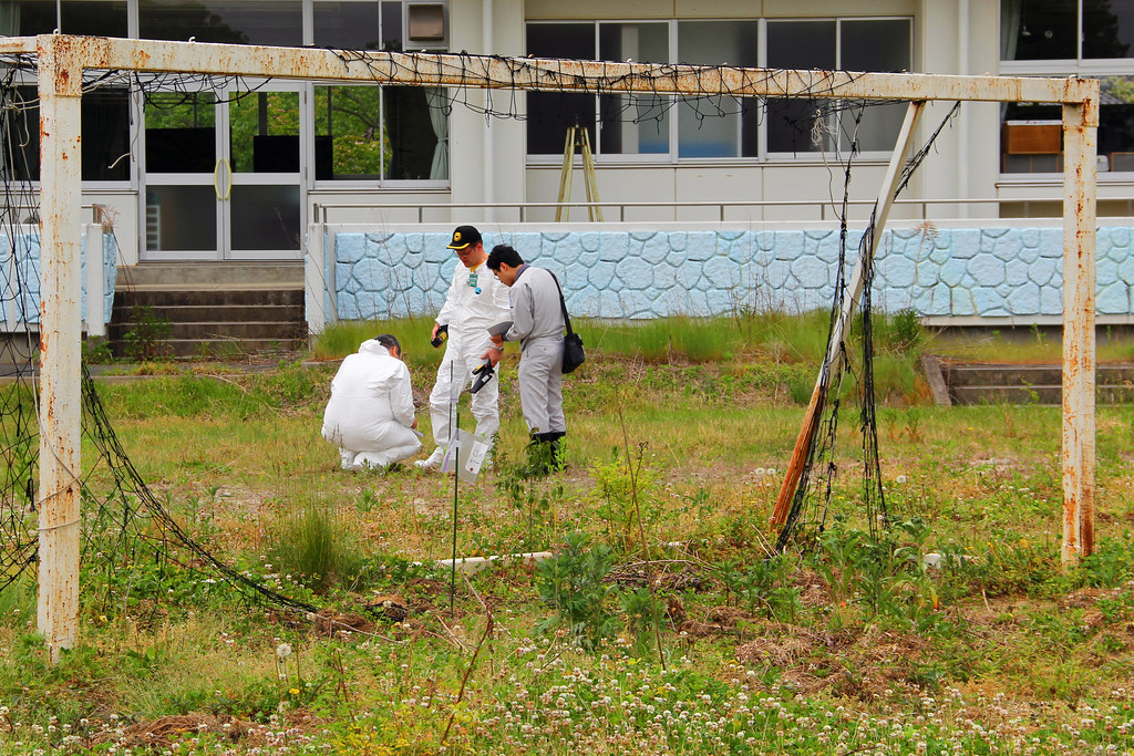 officials measuring radiation levels in Fukushima