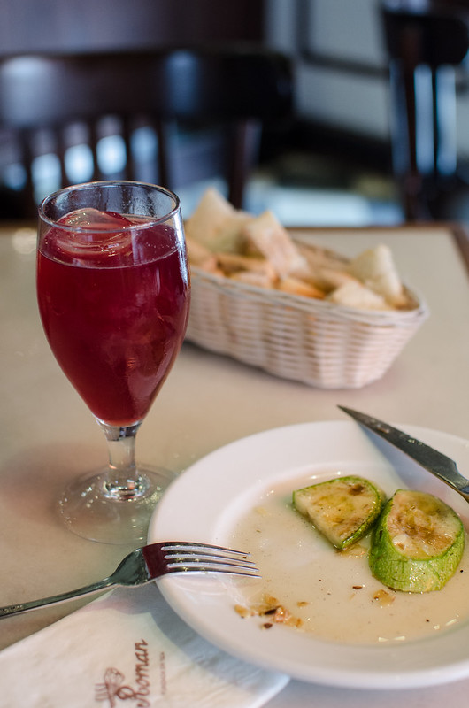 An appetizer of grilled zucchini and a tinto at Casa Roman in Seville, Spain